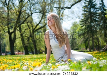 Smiling happy young person (teenager) sitting outdoors in blooming grassfiled and looking away - stock photo
