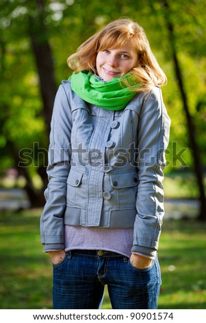 Smiling happy young woman at the park - stock photo