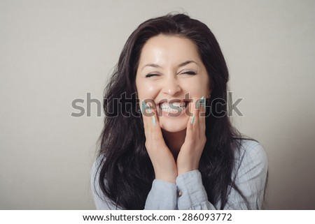 Smiling Happy young woman holding her hands on her face in and looking at the camera isolated on a gray background. - stock photo