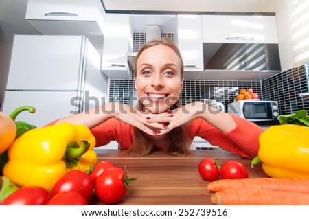 Smiling happy young woman in the kitchen with vegetables looking at camera - stock photo