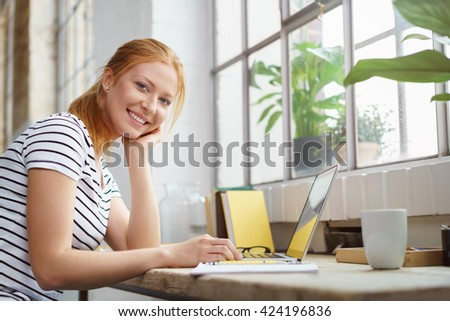 Smiling happy young woman studying at home sitting at a work table with her notes and laptop looking at the camera with a friendly grin