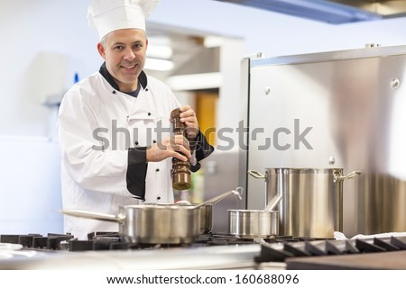 Smiling head chef flavoring food with pepper in professional kitchen - stock photo