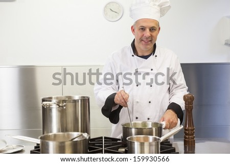 Smiling head chef holding ladle looking at camera in professional kitchen - stock photo