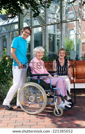 Smiling Health Care Professionals Taking Care an Elderly Patient in Wheel Chair. Captured Outdoor. - stock photo