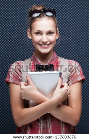 Smiling hipster girl holding tablet PC. Trendy teenager with tablet computer. Checkered red shirt and bow-tie - stock photo