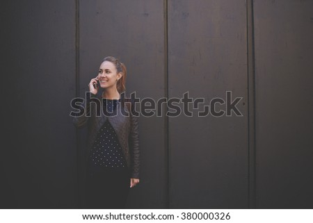 Smiling hipster girl talking on mobile phone while standing against brown street wall background with copy space for young advertising text message, young cheerful woman calling with cell telephone - stock photo