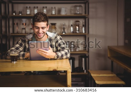Smiling hipster having coffee and using tablet computer at coffee shop - stock photo