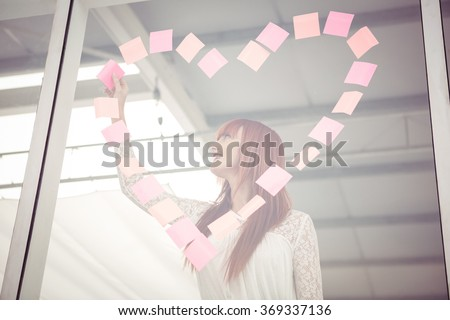 Smiling hipster woman doing a heart in post-it in office - stock photo