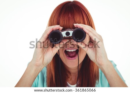 Smiling hipster woman looking through binoculars against white background