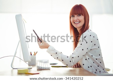Smiling hipster woman pointing screen with pen in her office - stock photo