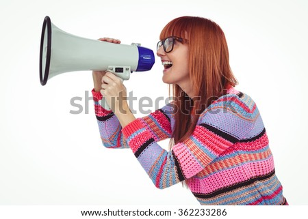 Smiling hipster woman shooting through megaphone against white background - stock photo