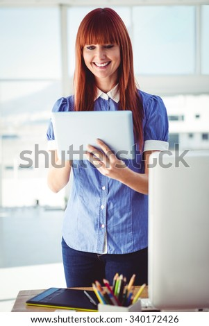 Smiling hipster woman using tablet in her office