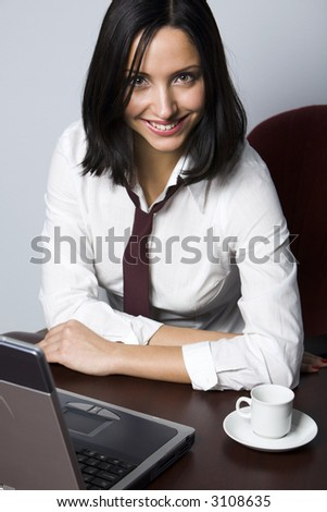 Smiling Hispanic brunette drinking coffee in front of her lap top - stock photo