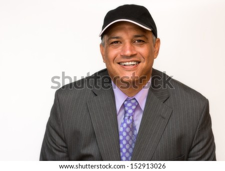 Smiling Hispanic man dressed in a business suit and wearing a cap. Space for some text in the hat. Happy business man with a positive gesture on his face.
