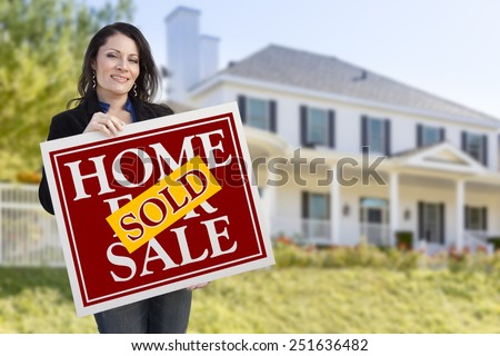 Smiling Hispanic Woman Holding Sold Home For Sale Sign In Front of Beautiful House. - stock photo