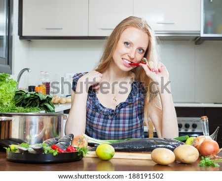 Smiling housewife is thinking how to cook  fish at kitchen