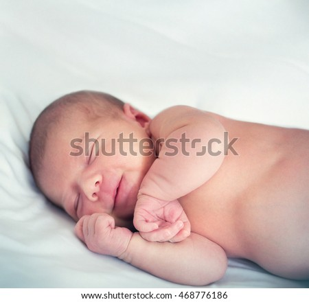 smiling in his sleep newborn baby on a background of white fabric