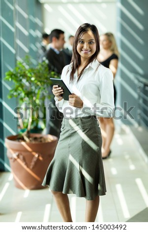smiling indian businesswoman holding tablet computer in office - stock photo
