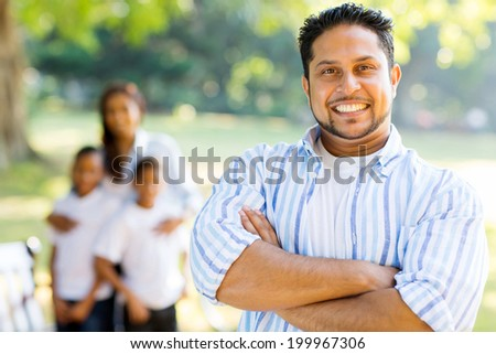 smiling indian father with arms crossed in front of family in the park