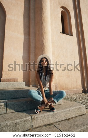 smiling indian lady in jeans, white shirt and white hat against ancient building. She is in harsh morning light. She is positive and playful. Building looks like church or eastern temple
