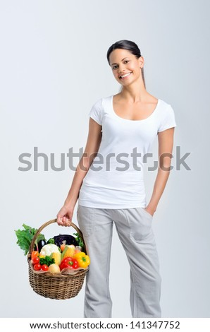 Smiling indian woman returning from the market, holding a basket full of fresh raw vegetables produce - stock photo