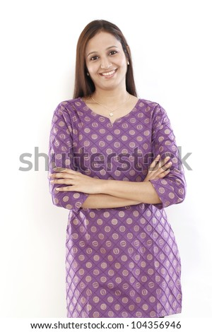 Smiling indian woman with arms crossed against white background - stock photo