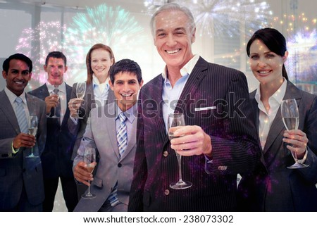 Smiling inernational business team holding glasses of Chamoagne against colourful fireworks exploding on black background - stock photo