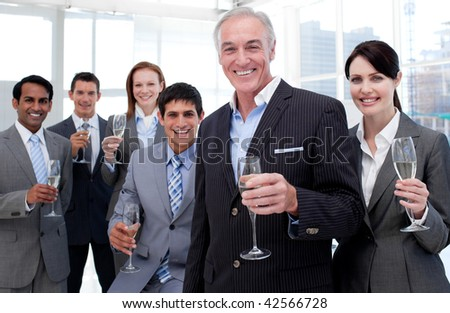 Smiling inernational business team holding glasses of Chamoagne to celebrate a success - stock photo