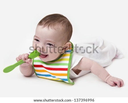 Smiling infant baby with spoon in mouth - stock photo