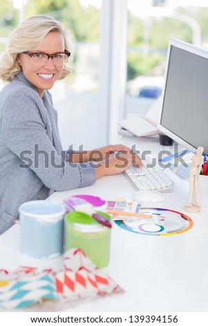 Smiling interior designer working on her computer with colour wheel and paint pots on her desk - stock photo