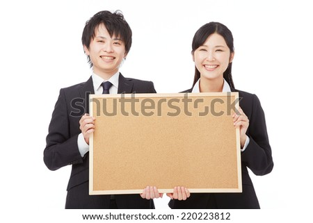 smiling Japanese businesswoman and businessman with Bulletin Board - stock photo