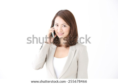 smiling Japanese businesswoman with the smart phone - stock photo