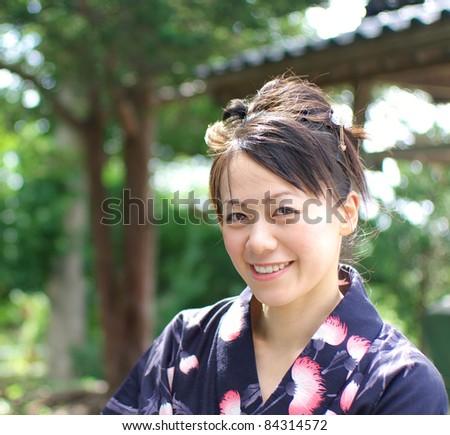 Smiling Japanese young woman in yukata - stock photo