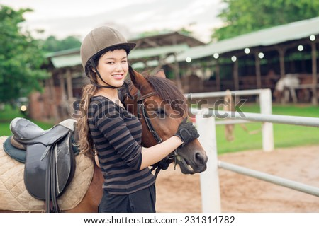 Smiling jockey girl stroking her horse - stock photo