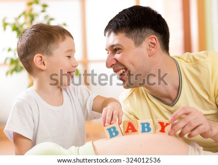 smiling kid boy and his dad playing with cubes on pregnant mother's belly - stock photo