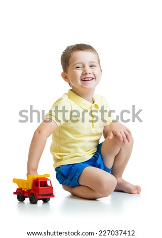 smiling kid boy playing with toy car - stock photo