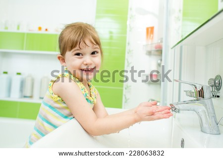Smiling kid child washing hands in bathroom - stock photo