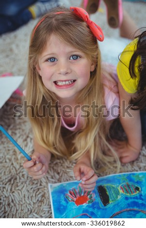 Smiling kid drawing pictures on paperon the floor - stock photo