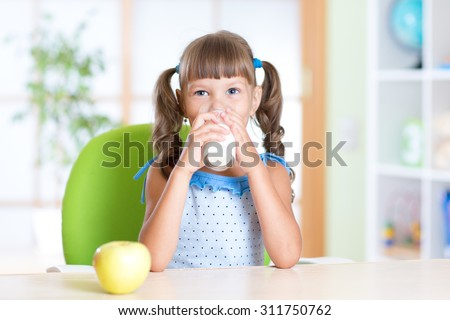 Smiling kid girl drinking milk from glass at home