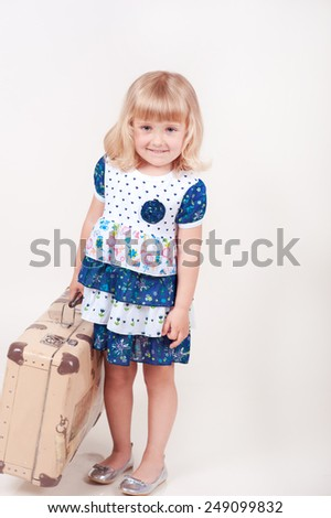 Smiling kid girl holding suitcase in room over white. Wearing stylish dress. Summer holiday vacation. Childhood.  - stock photo
