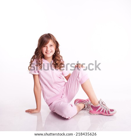 Smiling kid girl sitting on floor. Wearing sport clothes. Fitness exercise. Isolated over white - stock photo