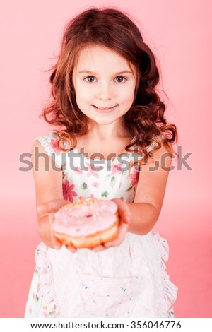 Smiling kid girl 5-6 year old holding glazed pink donut over pink. Looking at camera. Childhood.  - stock photo