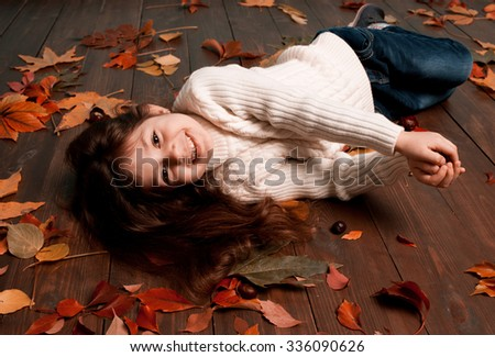 Smiling kid girl 5-6 year old playing with fallen leaves on wooden floor in room. Looking at camera. Childhood. Happiness. Cheerful. Seasoning.  - stock photo
