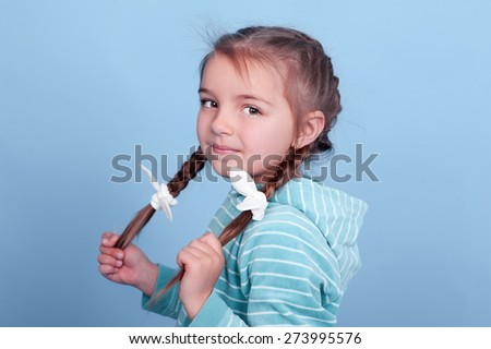 Smiling kid girl 3-4 year old posing over blue. Wearing blue striped hoodie. Looking at camera. - stock photo