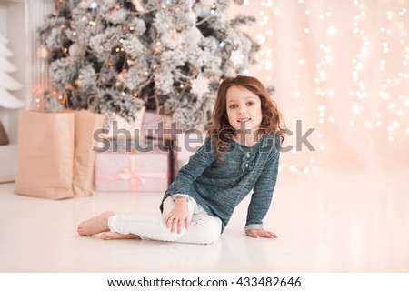 Smiling kid girl 4-5 year old sitting under christmas tree with presents and gifts in room. Wearing stylish clothes. Looking at camera. Celebration. Christmas lights. - stock photo
