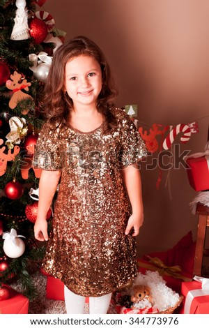 Smiling kid girl 4-5 year old standing over Christmas tree in room. Looking at camera. Cheerful. Happiness.