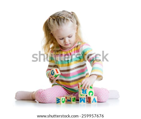 smiling kid little girl is building a toy block isolated - stock photo