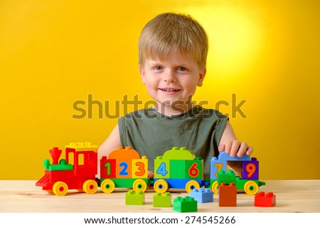 Smiling kid playing with bricks on the table on yellow background. ?oncept of early learning.