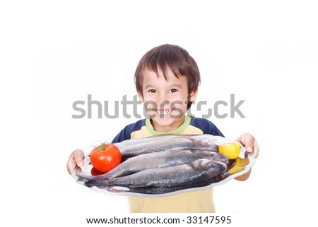 Smiling kid with fresh fish on table - stock photo