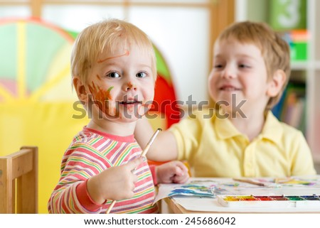 smiling kids boys paint at home or playschool - stock photo